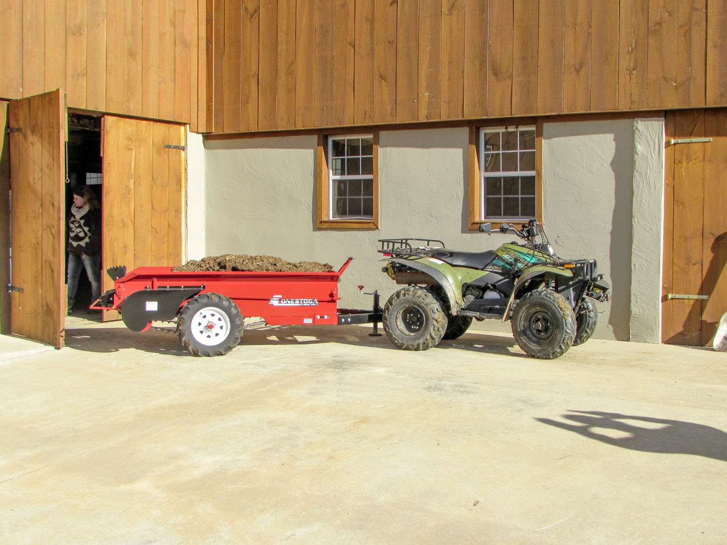 ground driven manure spreader being pulled by atv outside horse barn