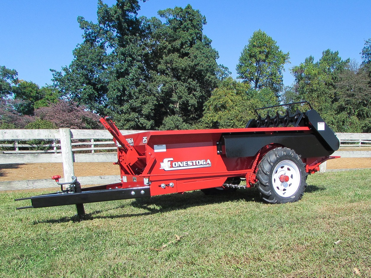 ground driven manure spreader sitting along white fence