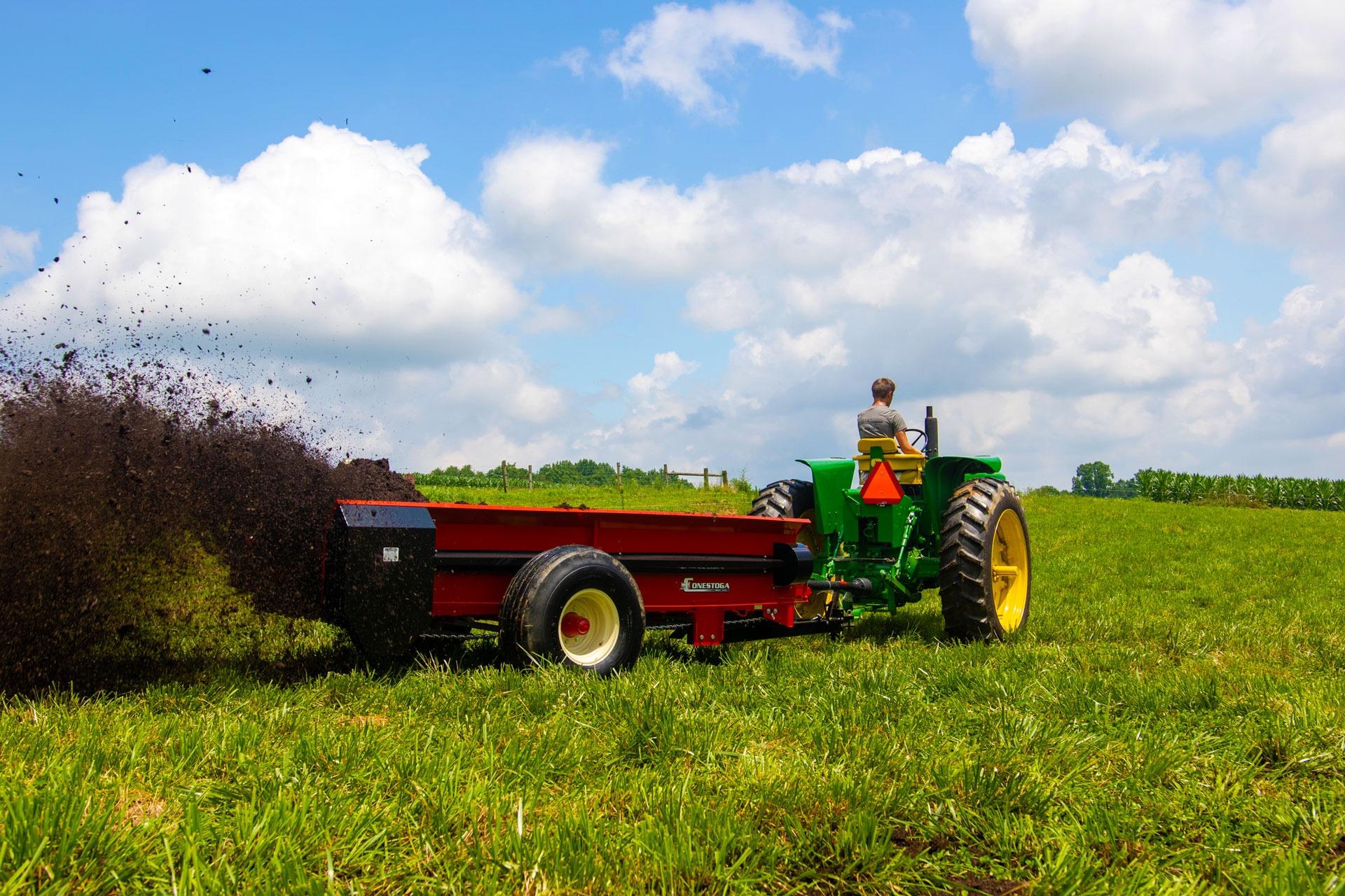 PTO farm manure spreader spreading in open field by conestoga manure spreaders.